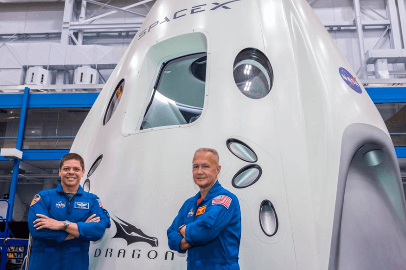 Two astronauts stand in front of a rocket